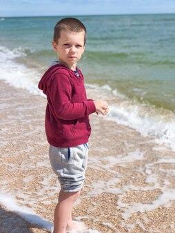Маленький мальчик в куртке и штанах в солнечный день стоит на берегу моря и смотрит в камеру. концепция отдыха и туризма.
