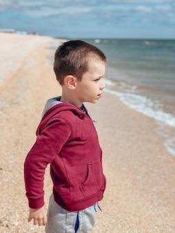 Маленький мальчик в куртке и штанах стоит на берегу моря и смотрит в сторону воды. концепция отдыха и туризма.