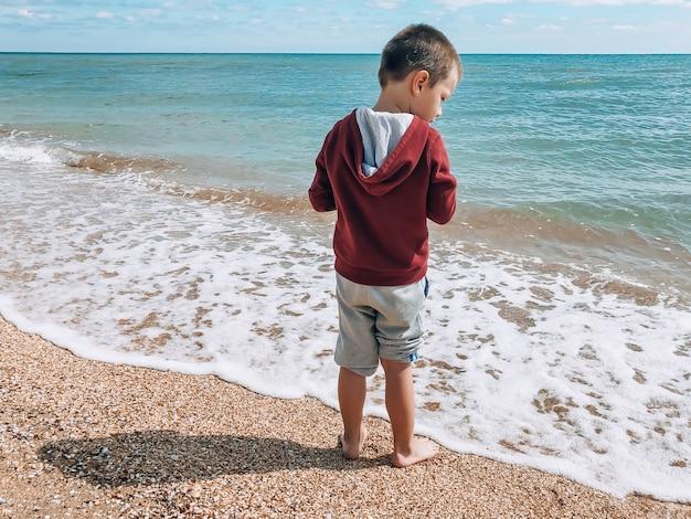 Маленький мальчик в куртке и штанах стоит на берегу моря спиной и смотрит в сторону воды. концепция отдыха и туризма.