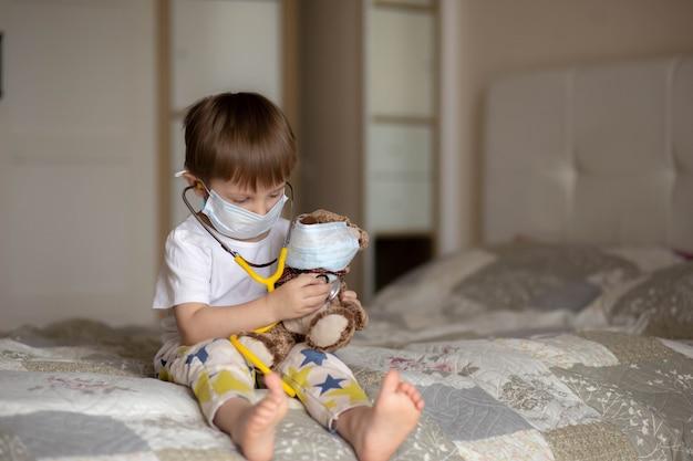 ベッドに座って聴診器でテディベアをしているマスクの小さな男の子。セレクティブフォーカスの画像。高品質の写真
