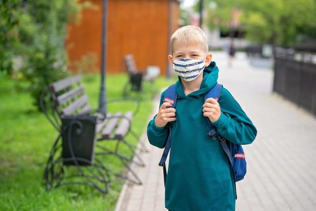 Маленький мальчик в защитной маске на лице и с рюкзаком на плечах