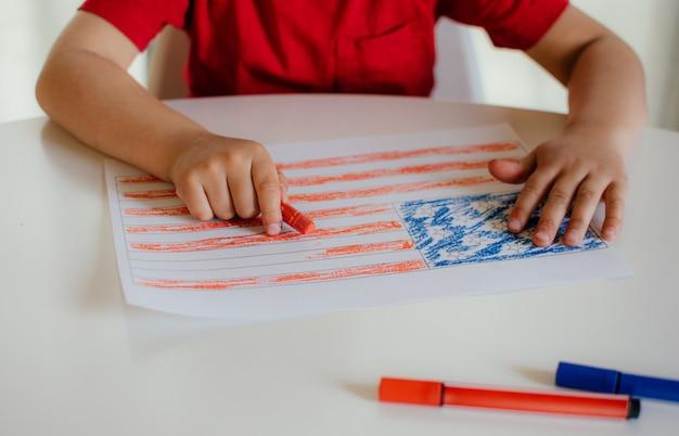 빨간 티셔츠를 입은 어린 소년이 흰색 테이블에 미국 국기를 그립니다. 미국 국기의 어린이 그림. 독립 기념일, 7 월 4 일.