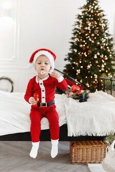 サンタクロースの衣装を着た小さな男の子が、クリスマスに飾られたインテリアのシャボン玉を膨らませます