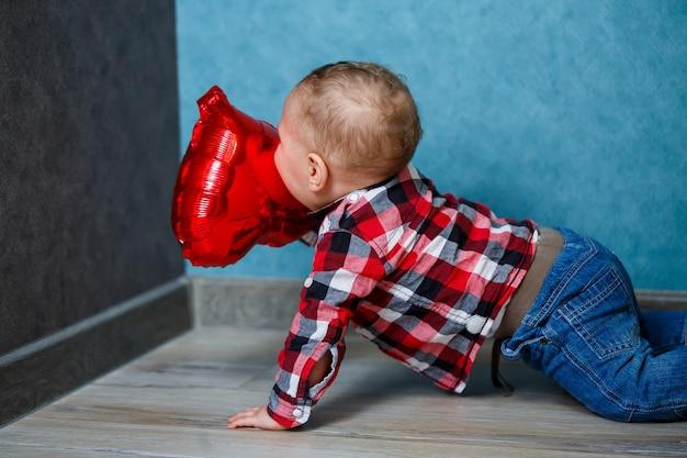 シャツを着た男の子がハートの形をした風船で遊ぶ