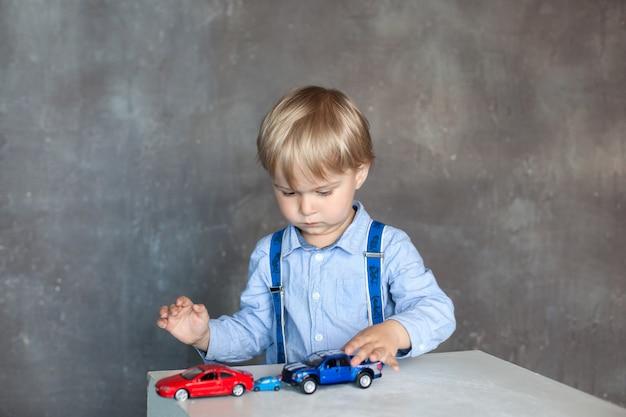 Маленький мальчик в рубашке с подтяжками играет с игрушечными разноцветными игрушечными машинками. мальчик дошкольного возраста, играя с игрушечный автомобиль на столе у себя дома или детский сад. развивающие игрушки для детей дошкольного и детского сада.