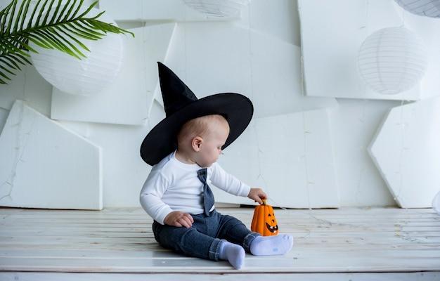 Маленький мальчик в костюме и черной шляпе сидит и играет с тыквой на белом фоне с копией пространства