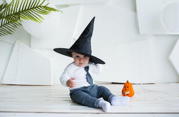 Маленький мальчик в костюме и черной шляпе сидит с тыквой на белом фоне с местом для текста