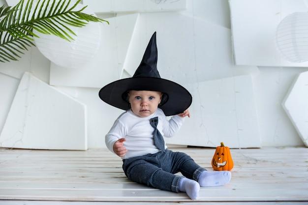 Маленький мальчик в костюме и шляпе сидит с тыквой на белом фоне с местом для текста