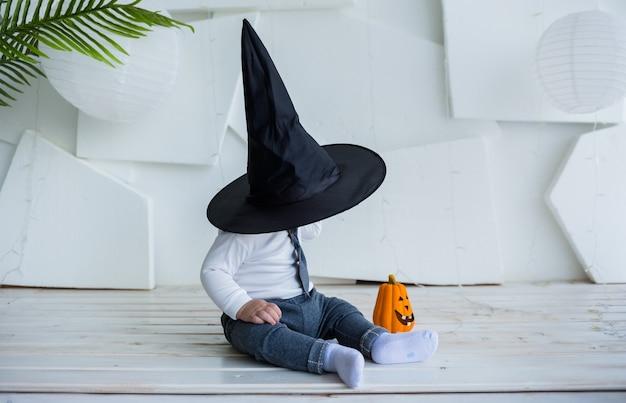 Маленький мальчик в костюме, накрывшись черной шляпой, сидит с тыквой на белом фоне с местом для текста
