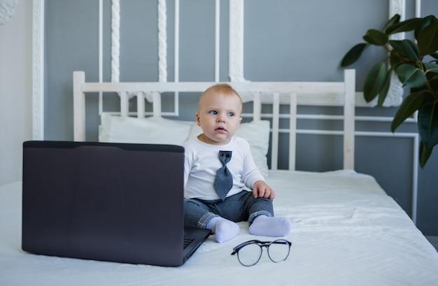 Маленький мальчик в костюме сидит на кровати с ноутбуком