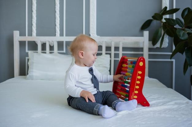 Маленький мальчик в костюме сидит с развивающей игрушкой на кровати