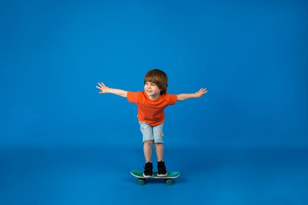Tシャツとショートパンツを着た小さな男の子が、テキスト用のスペースがある青い表面でスケートボードに乗る