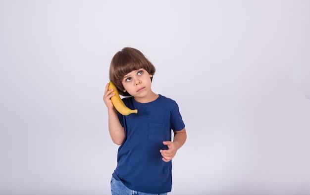Маленький мальчик в футболке держит банан на белом фоне с копией пространства