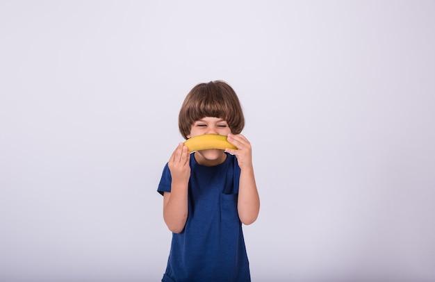 Маленький мальчик в футболке держит банан на белом фоне с местом для текста