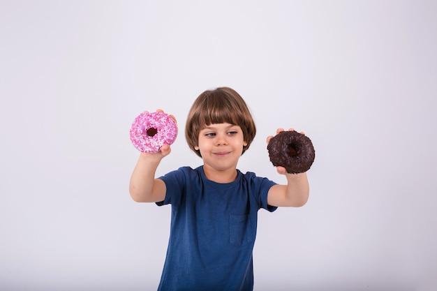 Tシャツを着た小さな男の子は、テキスト用の場所で白い背景に2つのドーナツを持っています
