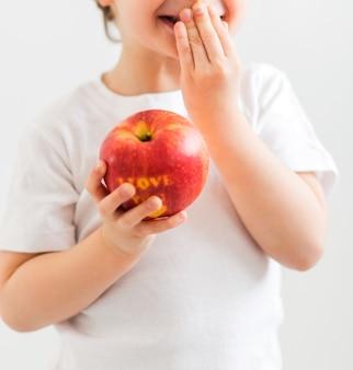 흰색 티셔츠를 입은 어린 소년이 내가 당신을 사랑한다는 비문으로 사과를 손에 들고 있습니다. 세로 사진