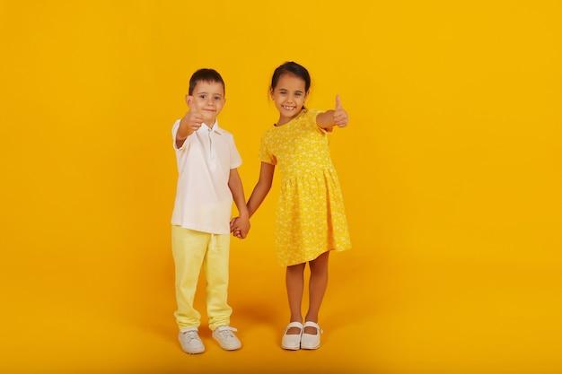 Маленький мальчик в белой футболке и желтых брюках держит за руку сестру в желтом платье.