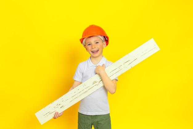 Маленький мальчик в оранжевом строительном шлеме на желтой стене, держа в руках деревянную доску, он счастлив и улыбается концепция развития ребенка строительства ремонта дома