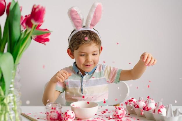 ウサギの耳の小さな男の子がイースターエッグを飾ります。イースターのコンセプト。春の季節