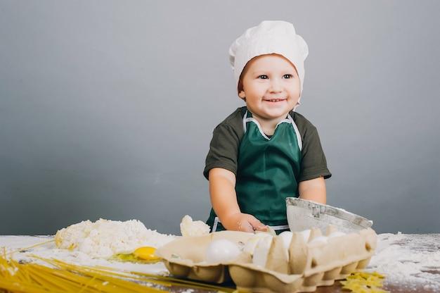 Маленький мальчик в поварской шляпе готовит обед