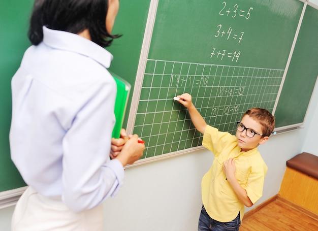 Маленький мальчик в очках пишет мелом на доске и смотрит на учителя на заднем плане ...