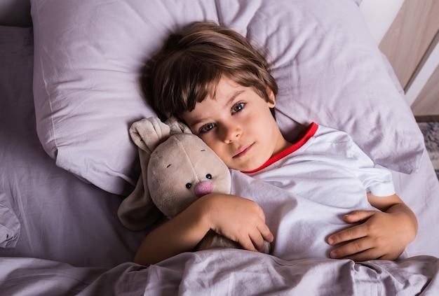 Маленький мальчик в пижаме проснулся на ватной подстилке на кровати с мягкой игрушкой.