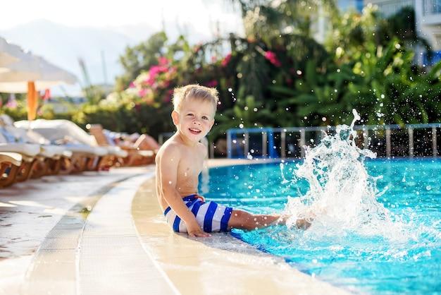 ホテルの隣のプールで足をはねかける縞模様のショートパンツの小さな男の子