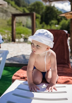 Маленький мальчик в плавках и белой панамской шляпе загорает на белом шезлонге на пляже