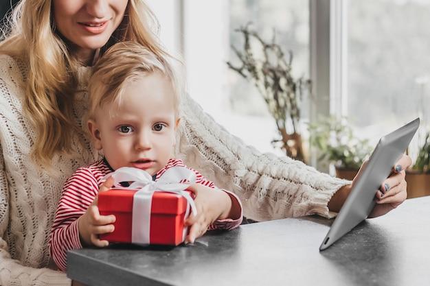 小さな男の子がプレゼントの入った赤い箱を持ってカメラを見ています。