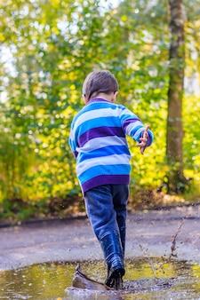 Маленький мальчик прыгает в луже.