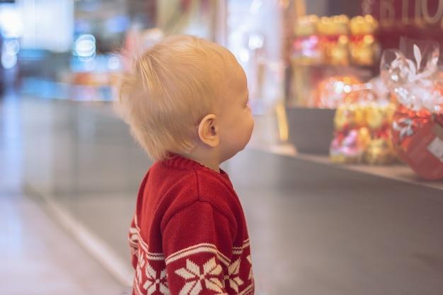 어린 소년이 쇼핑 센터의 상점 창에서 과자를 보고 있다