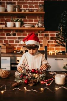 어린 소년이 빨간 크리스마스 모자를 쓰고 테이블에 앉아 자신의 손으로 크리스마스 화환을 만들고 있다