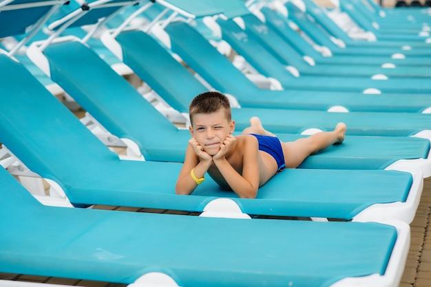 Маленький мальчик счастливо улыбается и загорает на шезлонге в солнечный день. счастливого отпуска. летний отдых и туризм.