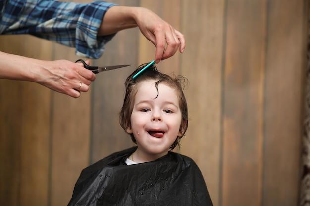 小さな男の子は彼の顔の美容師の明るい感情でトリミングされています