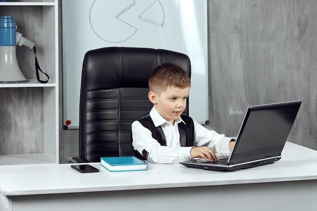 어린 소년이 사무실에서 노트북 작업을 하고 있다