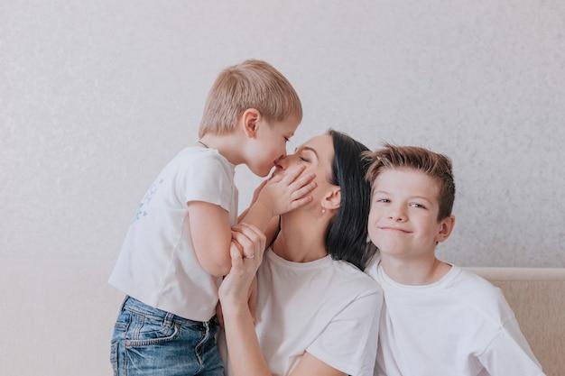 小さな男の子が母親の鼻にキスをし、クローズアップ、家族の幸せと愛、家族の相互理解。家族の喜びの概念。