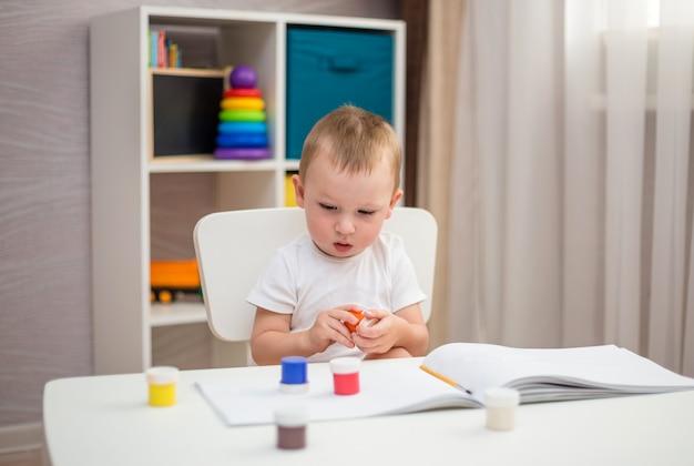 小さな男の子がペイントブラシでアルバムを描くことを学ぶ