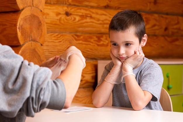어린 소년이 어머니를보고 실험이 어떻게 진행 될지 경청합니다.
