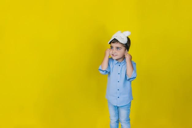 Маленький мальчик на ярко-желтой стене в модной маске для сна.