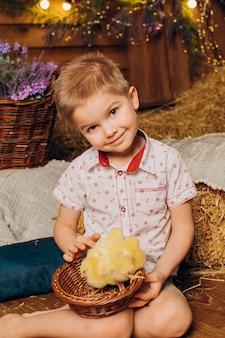 농장에 있는 어린 소년이 닭과 함께 건초 근처에 앉아 있다