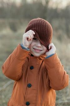 니트 모자를 가지고 노는 가을 날 거리에 어린 소년. 가을 공원에서 산책.