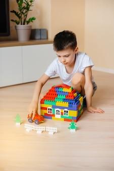 小さな男の子が建設キットで遊んで、家族全員のために大きな家を建てます。家族の家の建設。