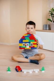 어린 소년이 건설 키트를 가지고 놀고 온 가족을 위해 큰 집을 짓습니다. 가족 주택 건설.
