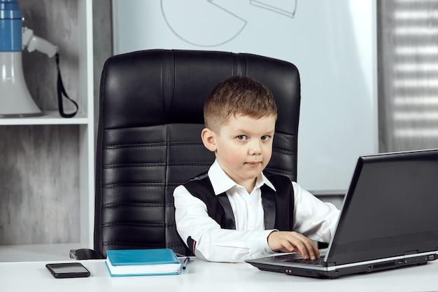 어린 소년이 사무실의 감독 책상에 앉아 포즈를 취하고 있다