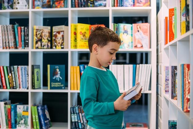 小さな男の子が本屋の子供向けの本の棚に手を伸ばす