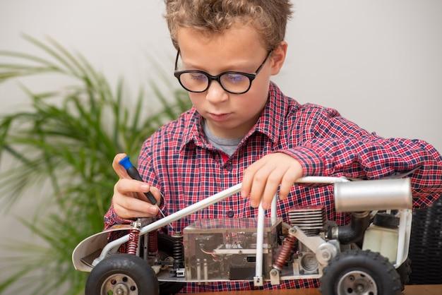 自宅でモデルのラジコンカーを修理している小さな男の子