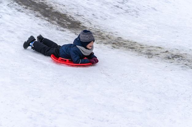 小さな男の子が冬の滑り台からそりに乗ります。冬休み。
