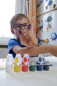 小さな男の子が絵の具で指を見せています。家庭での子供の創造性。