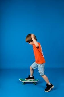 小さな男の子が横向きにテキスト用のスペースのある青い表面でスケートボードに乗る