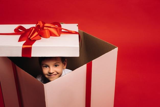 Маленький мальчик сидит в рождественском подарке и смотрит в него на красном фоне
